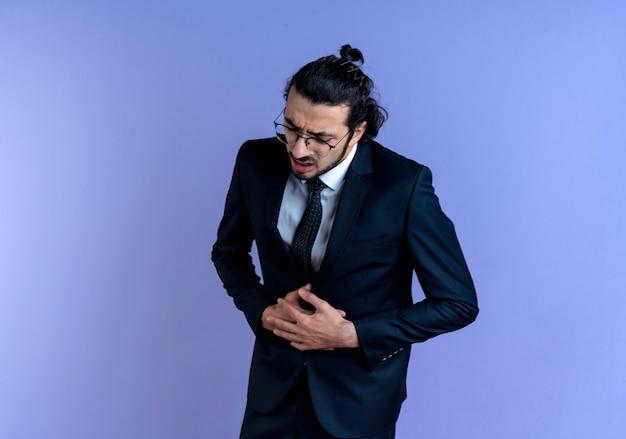 검은 양복과 안경에 비즈니스 남자가 파란색 벽 위에 서있는 복통을 갖는 그의 배를 만지고 몸이 좋지 않은 찾고