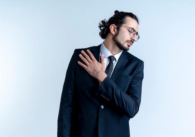 白い壁の上に立っている痛みを感じて彼の肩に触れて気分が悪いように見える黒いスーツと眼鏡のビジネスマン