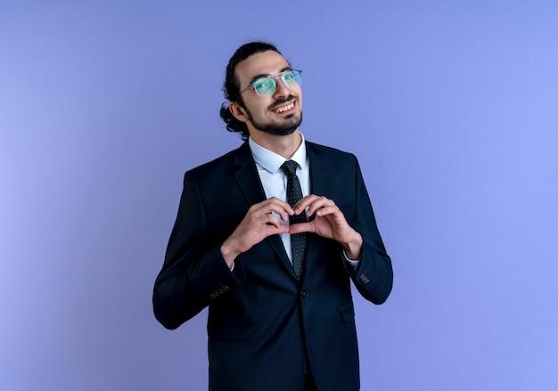 Деловой человек в черном костюме и очках, делая сердечный жест пальцами на груди, глядя вперед с улыбкой, стоит над синей стеной