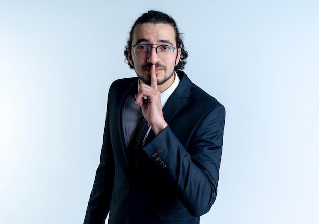 검은 양복과 흰 벽 위에 서있는 입술에 손가락으로 침묵 제스처를 만드는 안경 비즈니스 남자
