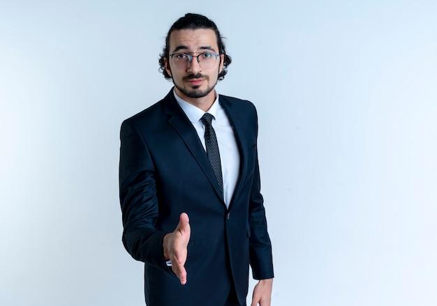 Деловой человек в черном костюме и очках, предлагающий приветствие рукой, выглядит уверенно, стоя над белой стеной