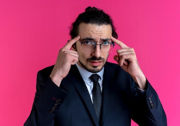 Деловой человек в черном костюме и очках, указывая на его виски, выглядит смущенным, стоя над розовой стеной