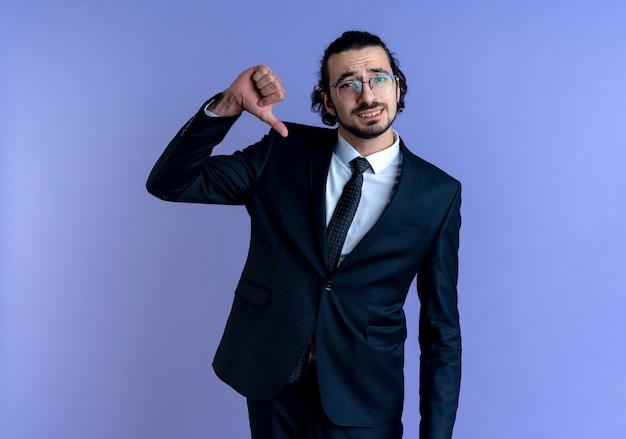 검은 양복과 안경에 비즈니스 남자가 파란색 벽 위에 서서 자기 만족을 앞을 찾고 자신을 가리키는