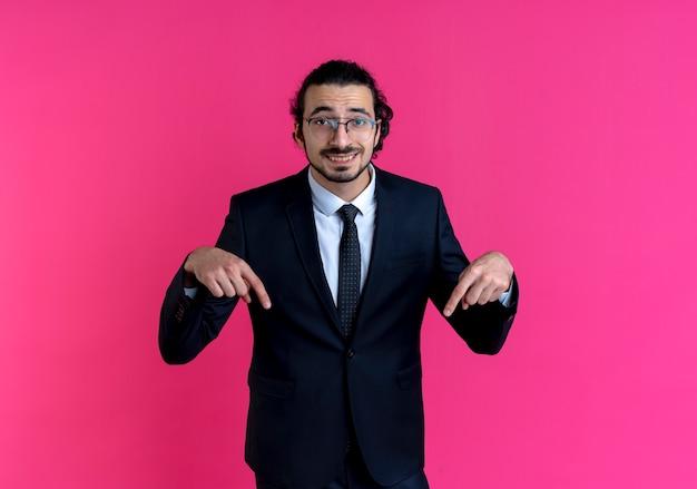 검은 양복과 분홍색 벽 위에 서 웃는 앞을 찾고 아래로 손가락으로 가리키는 안경 비즈니스 남자