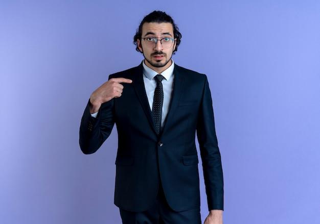 검은 양복과 파란색 벽 위에 서있는 혼란스러워 보이는 자신을 손가락으로 가리키는 안경 비즈니스 남자