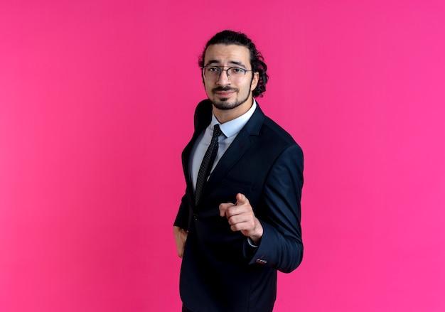 검은 양복과 분홍색 벽 위에 자신감 서를 찾고 앞을 손가락으로 가리키는 안경 비즈니스 남자