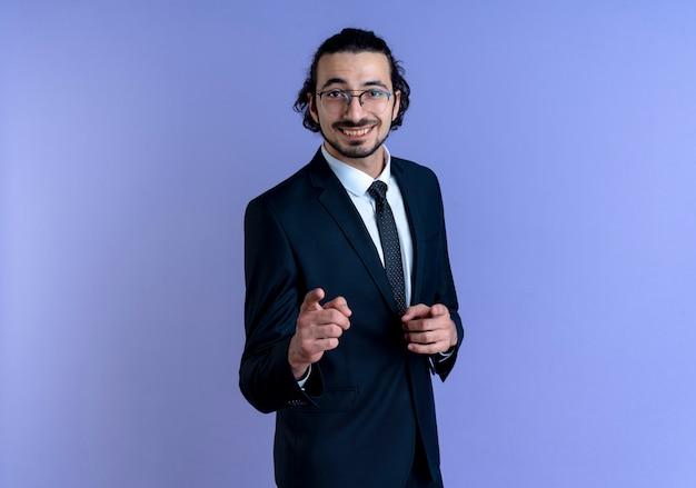 검은 양복과 파란색 벽 위에 유쾌하게 서있는 앞을 손가락으로 가리키는 안경 비즈니스 남자