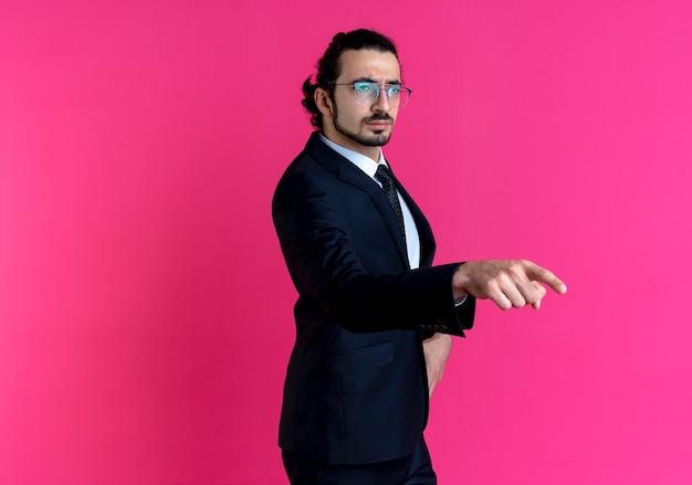 검은 양복과 분홍색 벽 위에 자신감 서 찾고 측면을 손가락으로 가리키는 안경 비즈니스 남자
