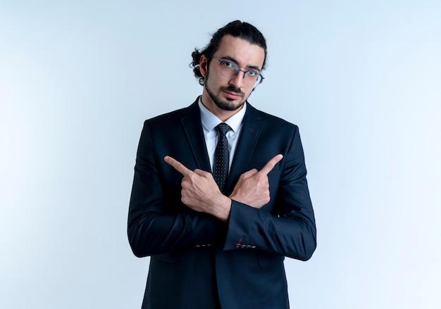 검은 양복과 흰 벽 위에 자신감이 서있는 측면을 손가락으로 가리키는 안경 비즈니스 남자