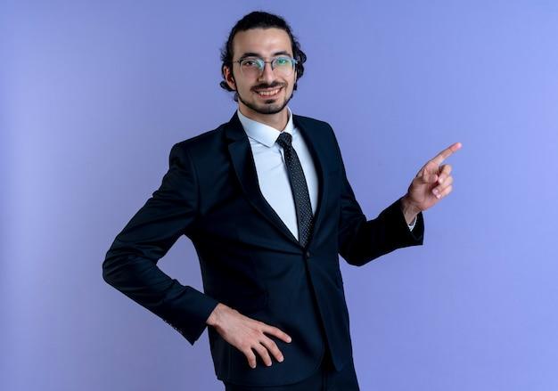 검은 양복과 파란색 벽 위에 유쾌하게 서있는 측면을 검지 손가락으로 가리키는 안경 비즈니스 남자