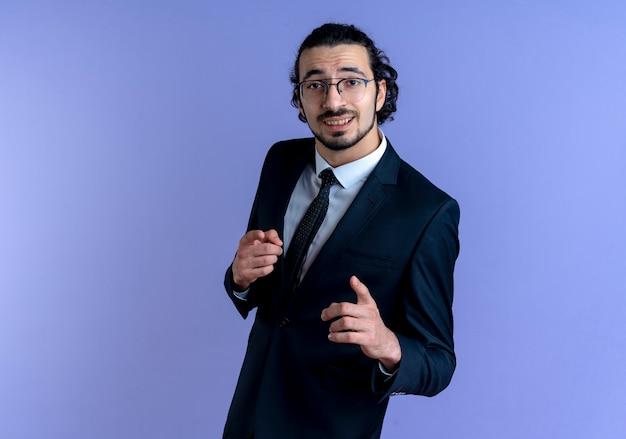 검은 양복과 파란색 벽 위에 서 웃는 앞을 검지 손가락으로 가리키는 안경에 비즈니스 남자