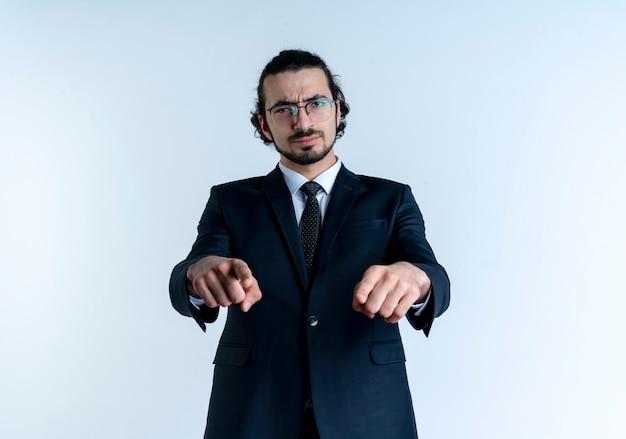 검은 양복과 흰 벽 위에 서있는 찡그린 얼굴로 앞을 검지 손가락으로 가리키는 안경 비즈니스 남자
