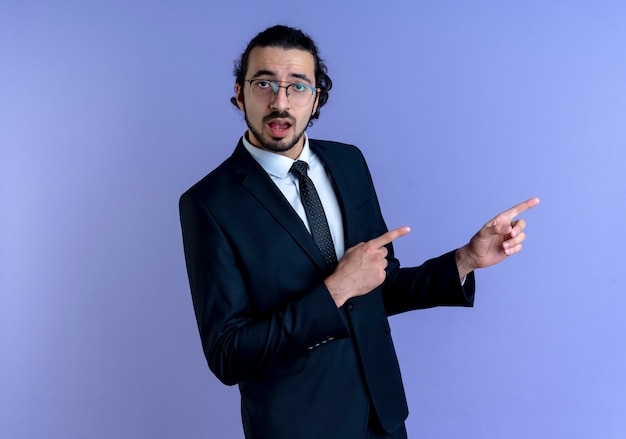 검은 양복과 파란색 벽 위에 서있는 혼란스러운 측면을 검지 손가락으로 가리키는 안경 비즈니스 남자
