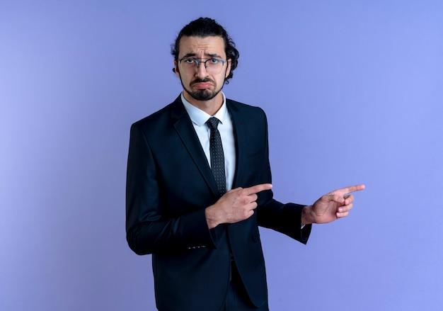 검은 양복과 파란색 벽 위에 서있는 슬픈 표정으로 혼란스러워 보이는 측면에 검지 손가락으로 가리키는 안경 비즈니스 남자