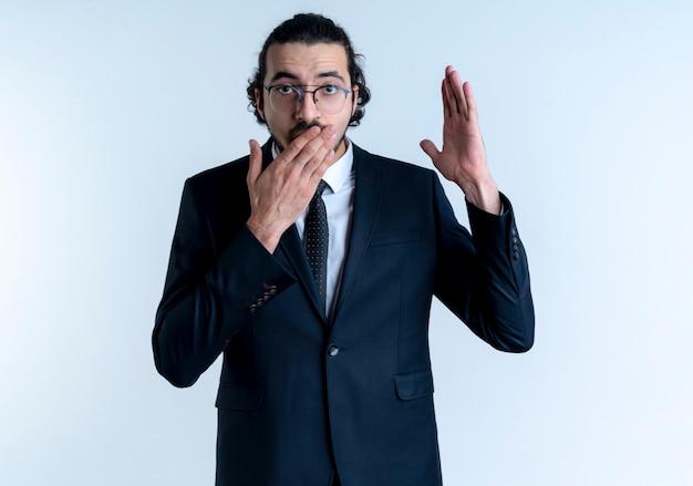 白い壁の上に立っている手で口を覆って驚いて見える手を上げる黒いスーツと眼鏡のビジネスマン