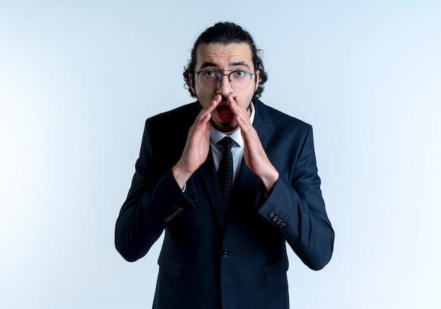 검은 양복과 흰색 벽 위에 서있는 입 근처 손으로 외치거나 전화하는 안경 비즈니스 남자