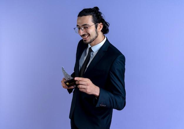 Деловой человек в черном костюме и очках показывает наличные и кредитную карту, весело улыбаясь, стоя над синей стеной
