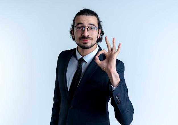 Деловой человек в черном костюме и очках показывает знак ок, уверенно улыбаясь, стоя над белой стеной