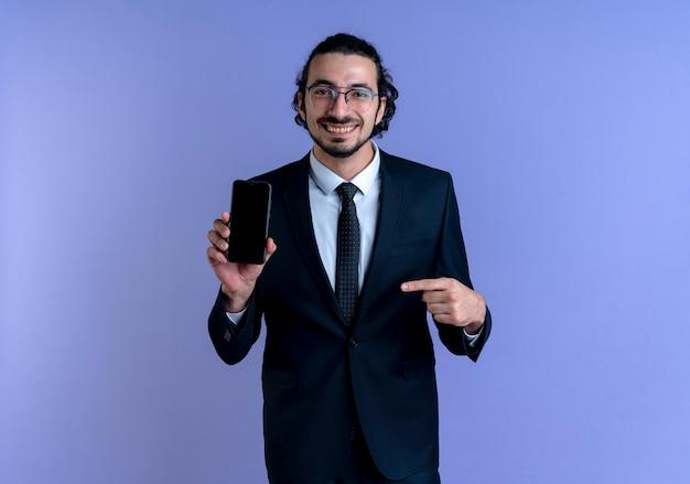 Деловой человек в черном костюме и очках показывает смартфон, указывая пальцем на него, уверенно улыбаясь, стоя над синей стеной