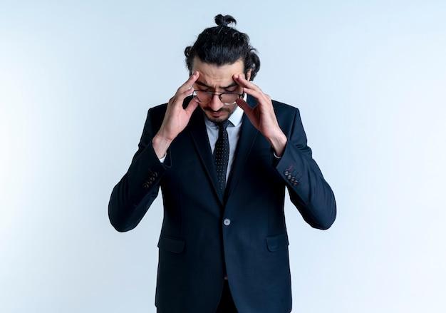 白い壁の上に立っている頭痛に苦しんで彼の寺院に触れる黒いスーツと眼鏡のビジネスマン
