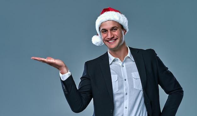 Деловой человек в рождественской шляпе, держащей копию пустое пустое пространство на ладонях, рекламирует скидку на продажу, изолированных на сером фоне и улыбается.