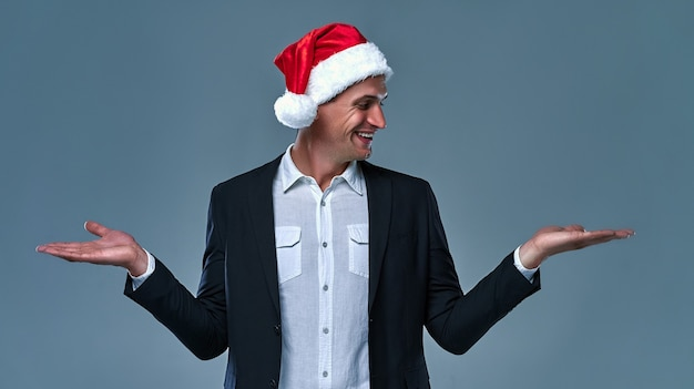 Деловой человек в рождественской шляпе, держащей копию пустое пустое пространство на двух ладонях, рекламирует скидку на продажу, изолированную на сером фоне и улыбается.