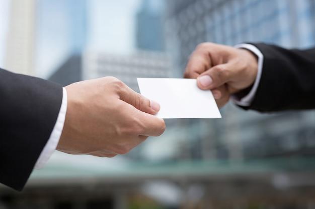 ビジネスマンを手に持つと、ビジネス上の連絡先を接続するために、名刺の空白の白いカードがモックアップされます。 Premium写真