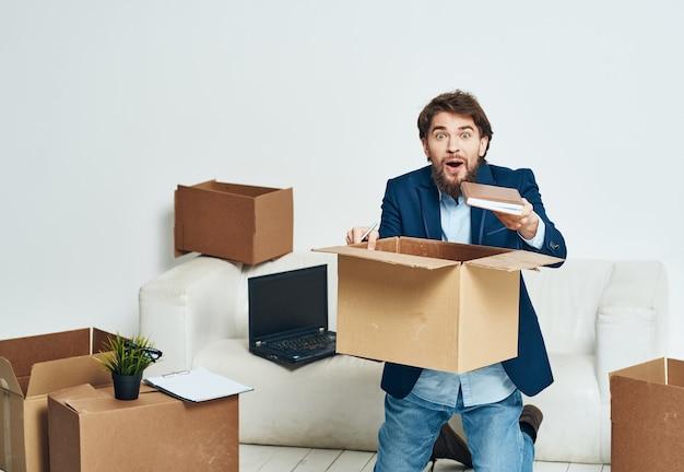 Деловой человек в офисных коробках для костюмов с вещами, движущимися в официальной упаковке ноутбука