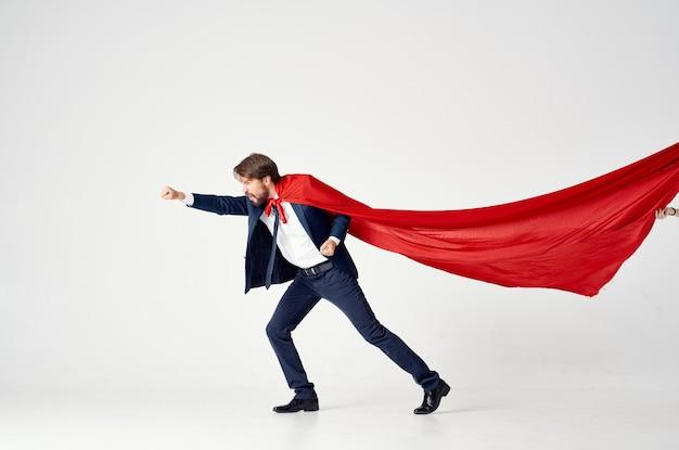 街のスーパーヒーローの仕事を保護する赤いマントのビジネスマン。高品質の写真