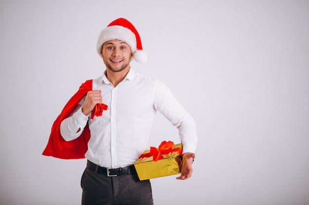 Бизнесмен в шляпе santa держа подарок на рождество изолированный