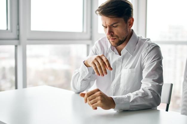 テーブルの事務作業に座っているシャツのビジネスマン