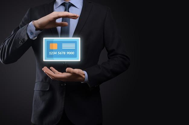 コンセプトバンキングと金融サービスを示す空白のクレジットカードアイコンを持っているスーツの手にビジネスマン。