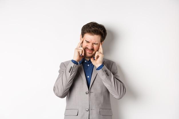 Деловой человек в костюме с головной болью, гримасой и касанием головы, страдает мигренью, болеет на белом фоне.