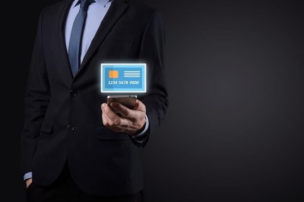 コンセプトバンキングと金融サービスを示す空白のクレジットカードアイコンを保持しているスーツのビジネスマン。