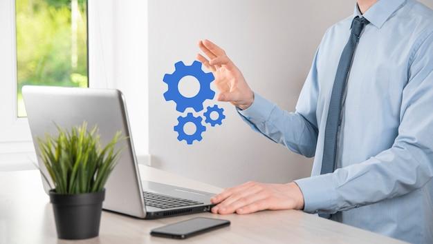 상호 작용 팀워크 개념을 나타내는 금속 기어와 톱니바퀴 메커니즘을 들고 있는 정장을 입은 사업가, 가상 톱니바퀴의 손을 잡고 있습니다.