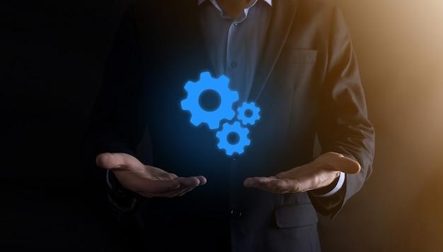 Деловой человек в костюме, держащем металлические шестерни и механизм зубчатых колес, представляющий концепцию совместной работы взаимодействия, ручную группу виртуальных зубчатых колес.