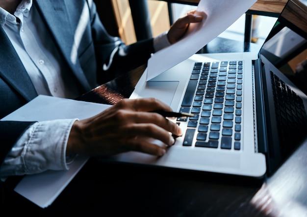 本の仕事の通信技術とラップトップの前でスーツを着たビジネスマン