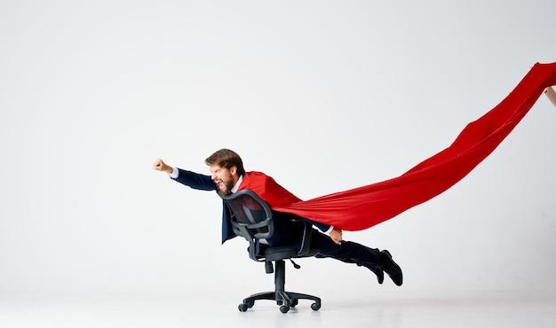 スーツオフィスチェア赤いマントのスーパーヒーローのビジネスマン