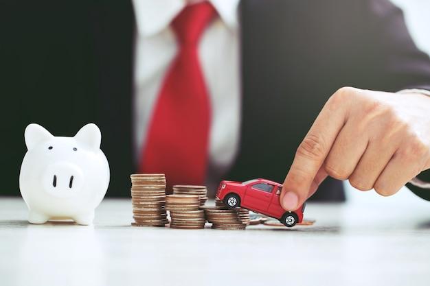 Деловой человек в костюме с открытой ладонью поддерживает модель игрушечной машинки с большим количеством денег в страховом ссуде