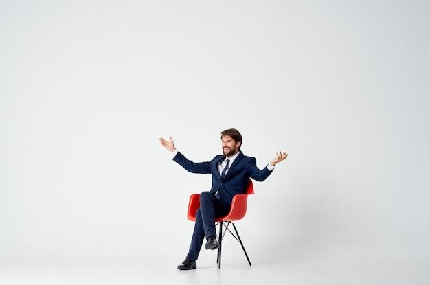 Деловой человек в костюме, сидя на красном стуле, эмоции офисного развлечения