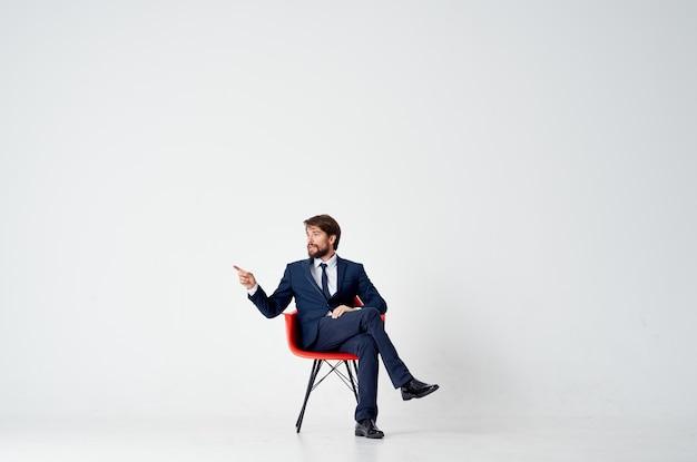 Деловой человек в костюме, сидя на красном кресле в офисе эмоций