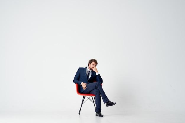Деловой человек в костюме, сидя на красном стуле, финансовый менеджер