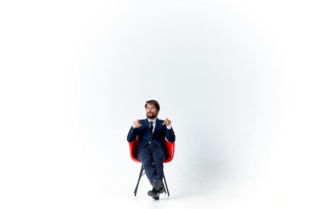 Деловой человек в костюме, сидя на красном стуле, финансовый офис-менеджер
