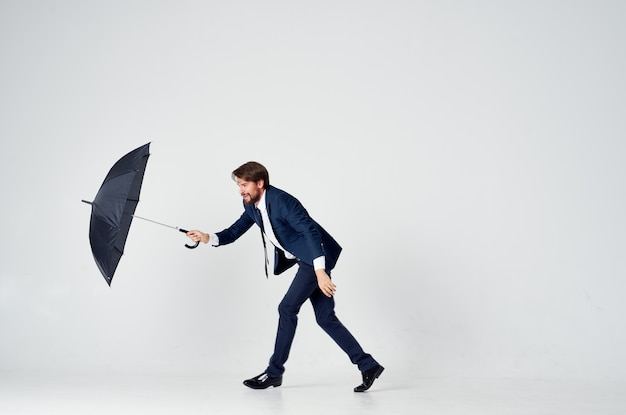 Деловой человек в костюме с зонтиком, защита от дождя, элегантный стиль, светлый фон