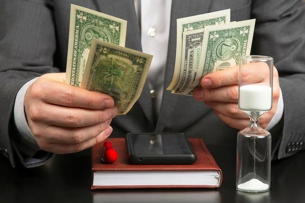 Деловой человек в офисе считает деньги на фоне песочных часов. бизнес и вознаграждение.