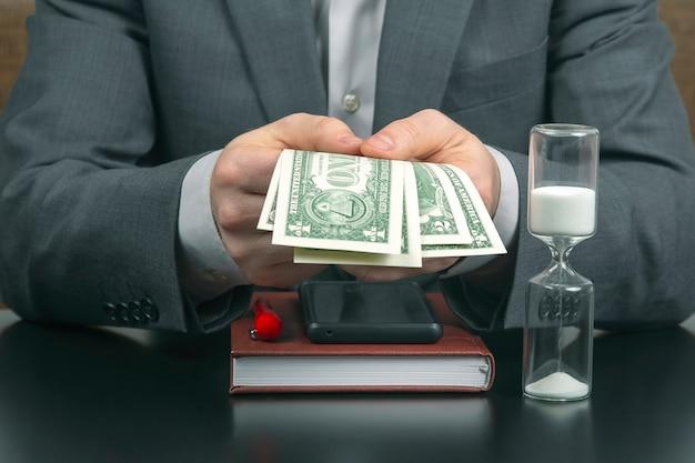 사무실에서 사업가는 해시계에 돈을 계산합니다. 사업과 보수.