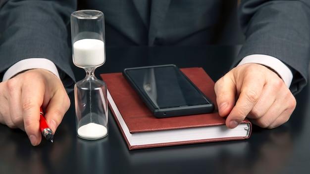 Деловой человек в офисе работает на фоне песочных часов. бизнес и успешная цель