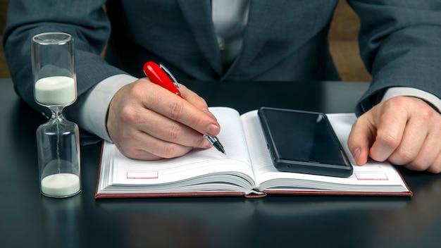 オフィスのビジネスマンは携帯電話と砂時計で働いています。ビジネスと成功の目標