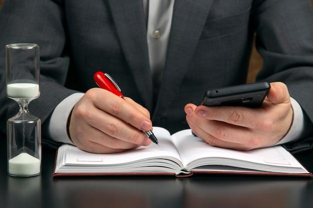 オフィスのビジネスマンは砂時計の上の携帯電話で働いています。ビジネスと成功の目標