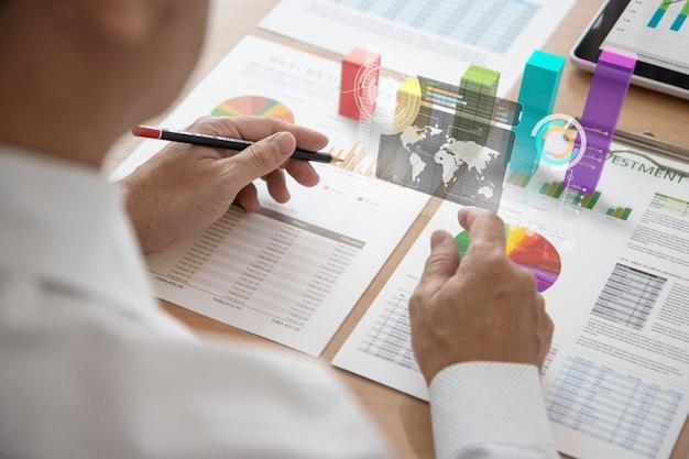 Деловой человек взаимодействует, касаясь футуристического экрана дополненной реальности, анализируя или рассматривая результаты бизнеса и анализ инвестиций или окупаемости инвестиций